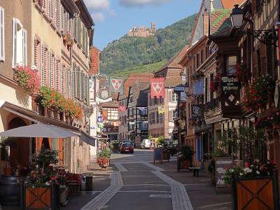 Ribeauville la grand rue et le chateau de saint ulrich en arriere plan route des vins d alsace guide du tourisme de l alsace
