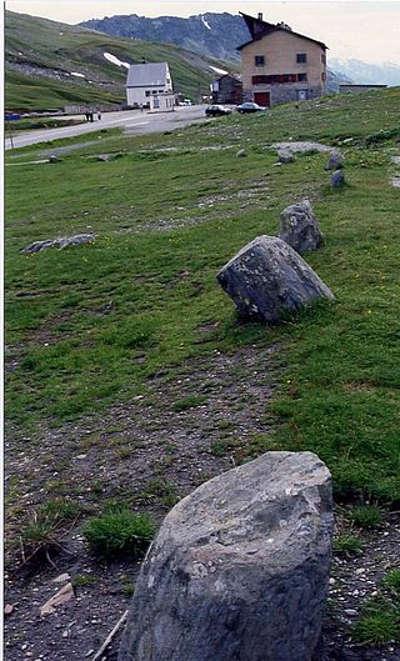 Col du petit saint bernard au premier plan les pierres du cromlec h au milieu de la route l ancienne douane routes touristiques de savoie guide touristique de rhone alpes