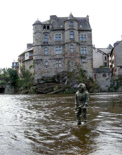 Espalion statue de scaphandrier devant le vieux palais routes touristiques de aveyron guide du tourisme midi pyrenees